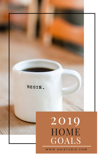 "image of white mug with black ""begin."" written on it; sitting on wood table with wood chairs in background. text box says 2019 home goals."
